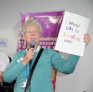 A woman speaking at a co-production group meeting. She is holding a microphone and a piece of paper which reads 'I would like to socialise more.'