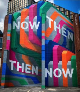 A building has colourful graffiti saying Now and Then, Then and Now